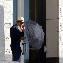An Amish man takes a smoke break outside the U.S. Federal Courthouse in Cleveland on Wednesday, Sept. 19, 2012.  The jury finished their fourth day of deliberations without a verdict in the trial of 16 people accused of hate crimes in hair- and beard-cutting attacks against fellow Amish in Ohio.
