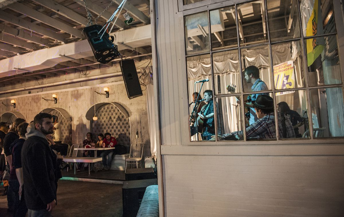 Inside of Swan Dive, the venue has off white walls, with a wall of glass windows next to the band and some nooks with booths.