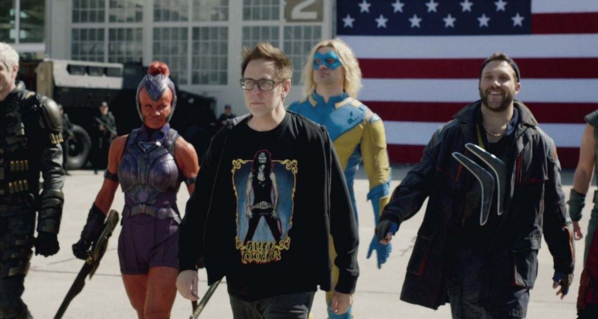 James Gunn is flanked by several actors on the set of The Suicide Squad.