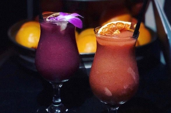 Two frozen cocktails on a dark background. One is purple and garnished with an orchid; the other is pink and garnished with an orange slice.