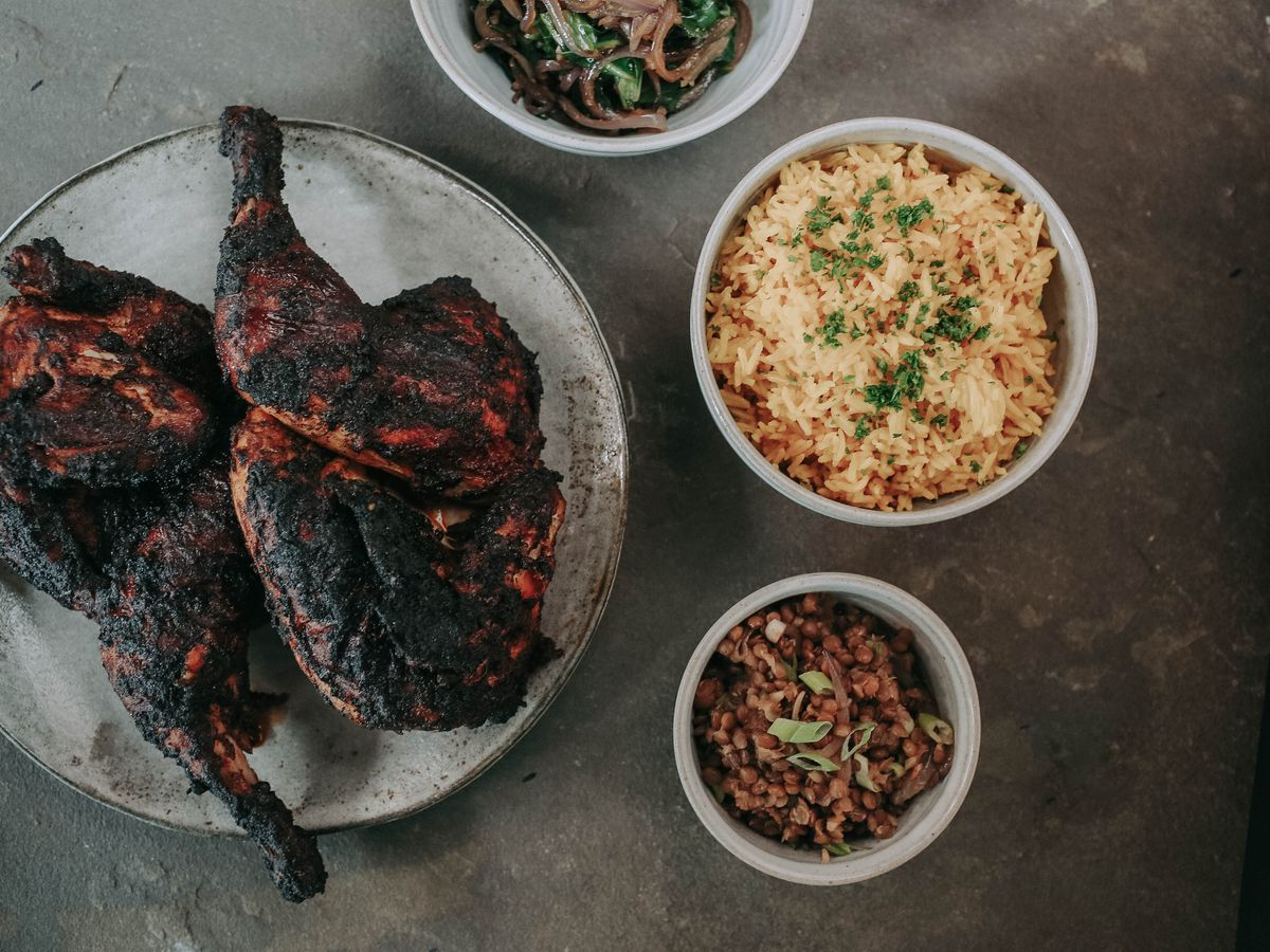 A plate of grilled berbere-spiced chicken next to a bowl of rice and other sides
