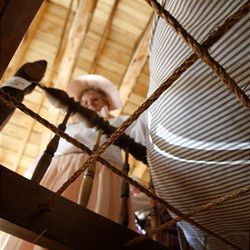Dawn Warenski pulls back the straw-stuffed mattress to show the crossed ropes that provide support on the old bed at the Daughters of the Utah Pioneers historic cabin in Santaquin.