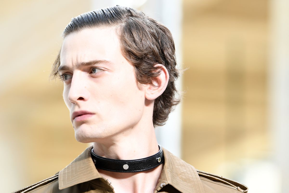 A model walks the runway wearing a leather choker necklace.