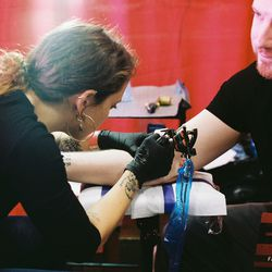 """Brooklyn-based tattoo artist Carina Novello tattoos a fan at SopranosCon. Throughout the weekend, she tattooed<em>Sopranos</em>flash including Christopher in a neck brace, Paulie Walnuts's face, and Tony strangling an FBI informant in the Season 1 episode """"College."""""""