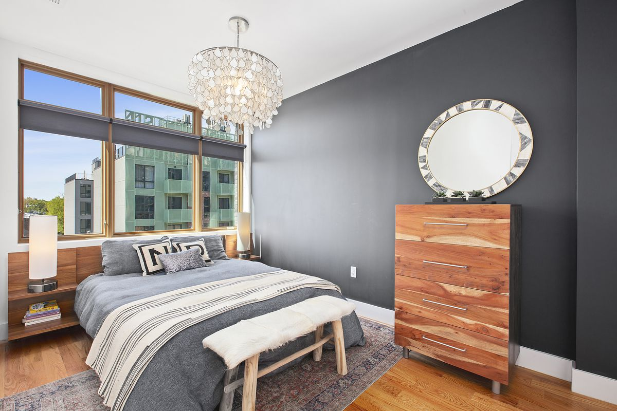 A bedroom with a black wall, a large window, a chandelier, and a medium-sized bed.