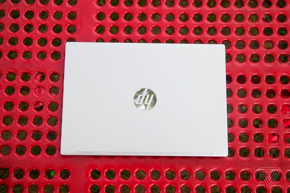 The lid of the HP Pavilion Aero 13 on a red picnic table seen from above.