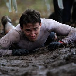A competitor crawls through mud during the Tough Guy Challenge on January 27, 2013 in Telford, England.