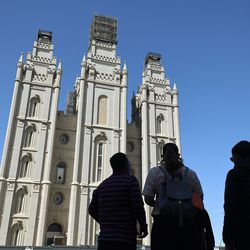 Tourists stand near the Salt Lake Temple, which is currently under renovation, during the 191st Annual General Conference of The Church of Jesus Christ of Latter-day Saints in Salt Lake City on Saturday, April 3, 2021.