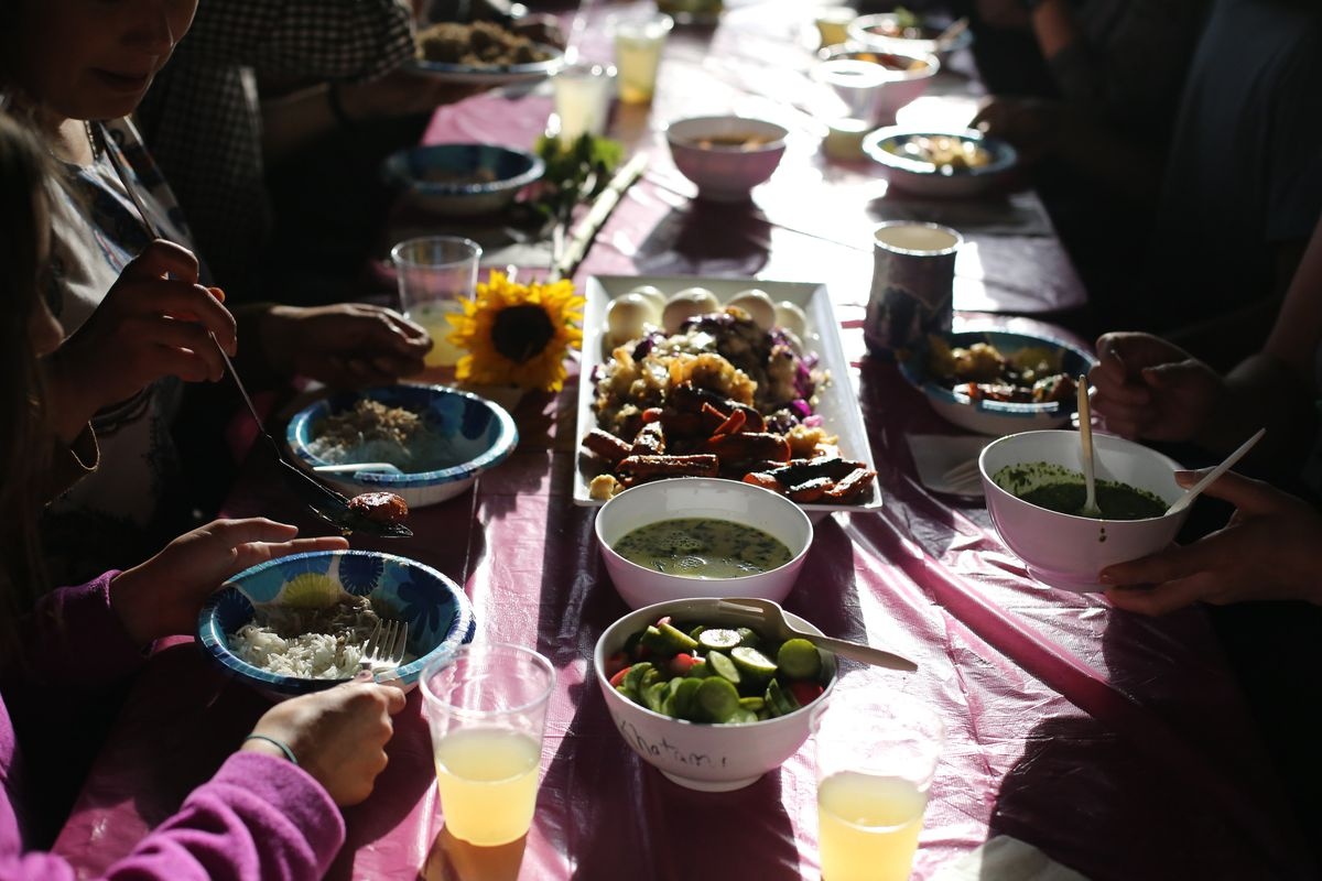 A community table with food, drinks, and flowers, illustrating FEEST, a Seattle-based organization of young BIPOC leaders