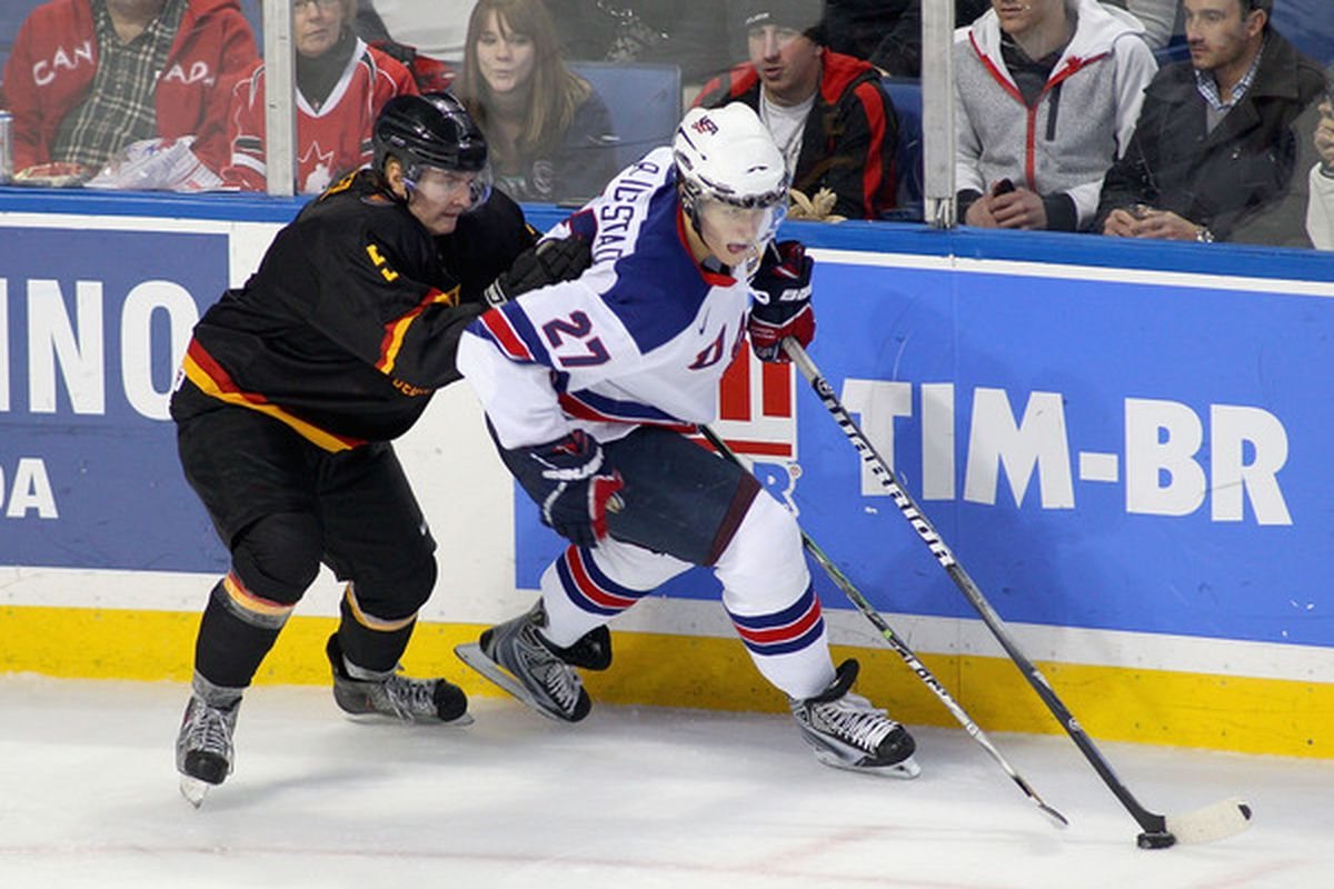 Panthers prospect Nick Bjugstad #27 of the United States skates ahead of Germany's Ben Hufner during the 2011 IIHF World U20 Championship game, December 30 2010 in Buffalo.