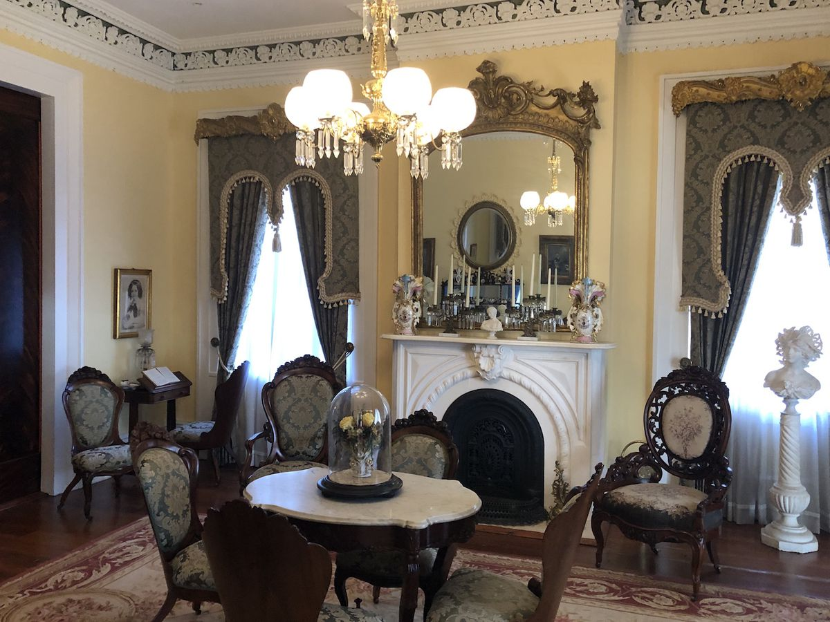 Formal parlor with table and chairs in foreground and elaborate fireplace in background.