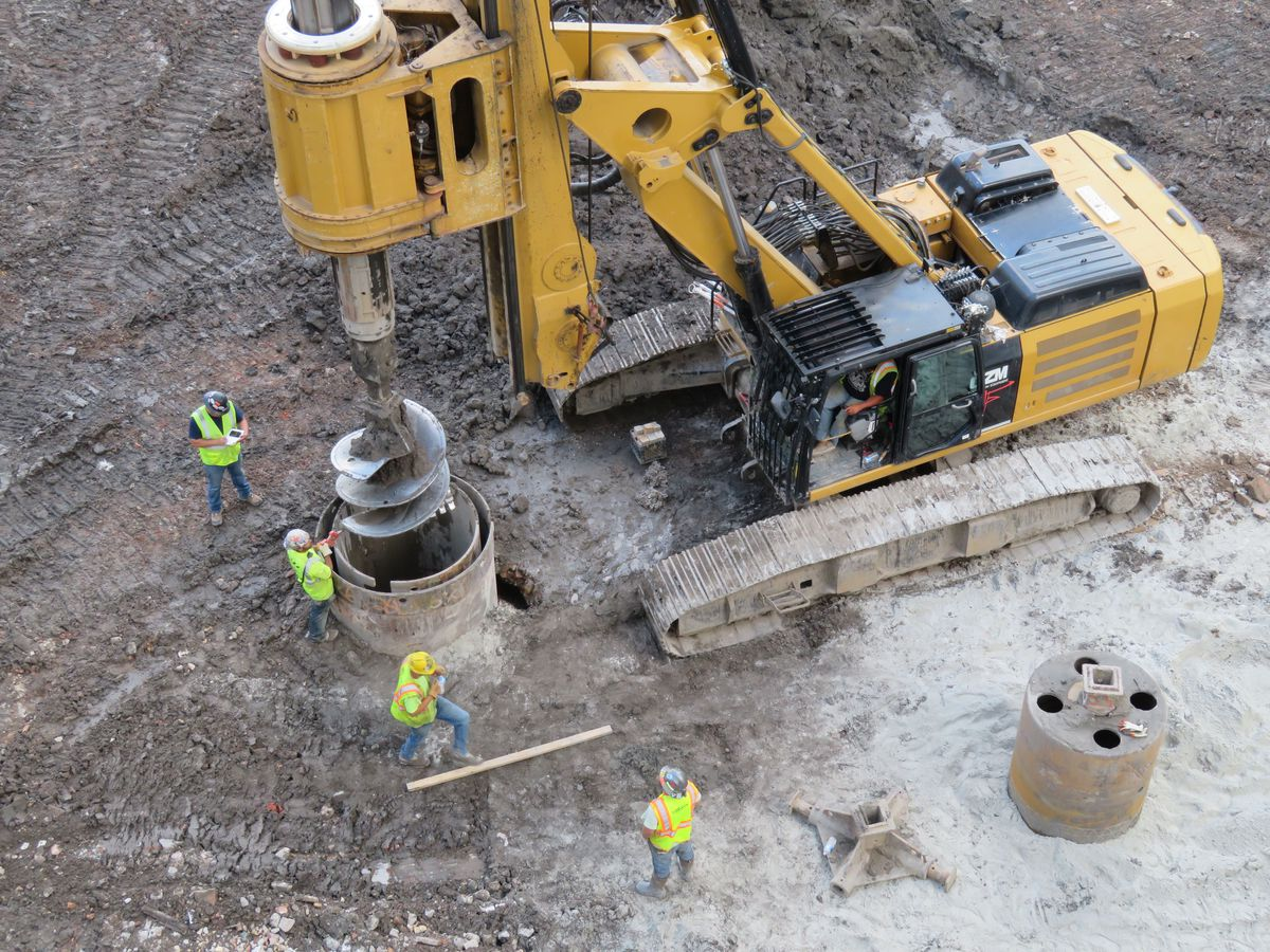 An overhead shot of four construction workers standing around a drilling machine making a hole in the the earth.
