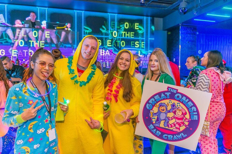 People in onesies at neon-lit bar