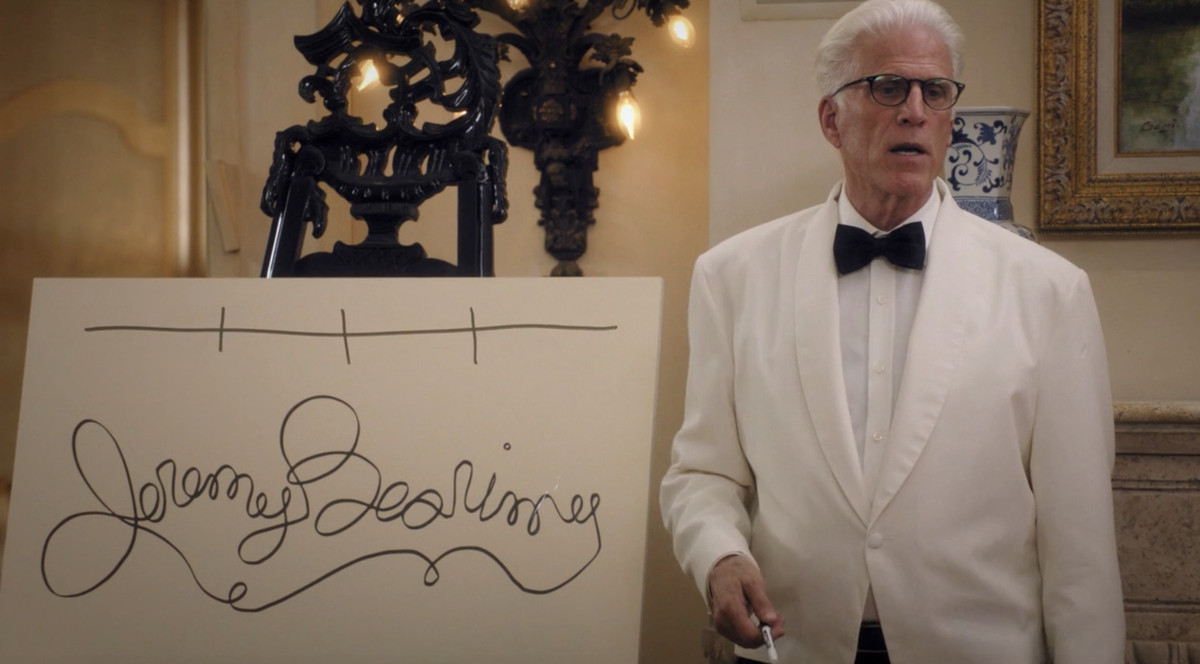 """Ted Danson as Michael standing next to a whiteboard that reads """"Jeremy Bearimy"""" in cursive"""