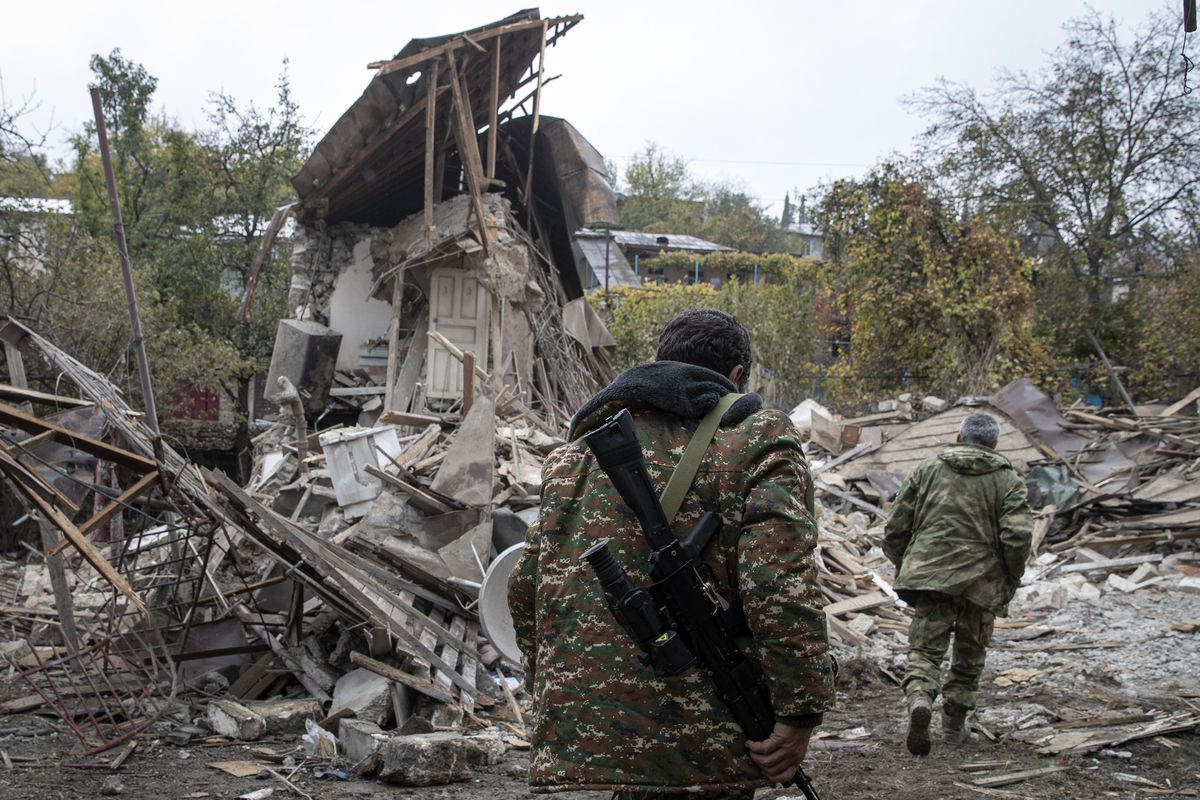A person in camouflage carrying a gun walks past the ruins of a house.
