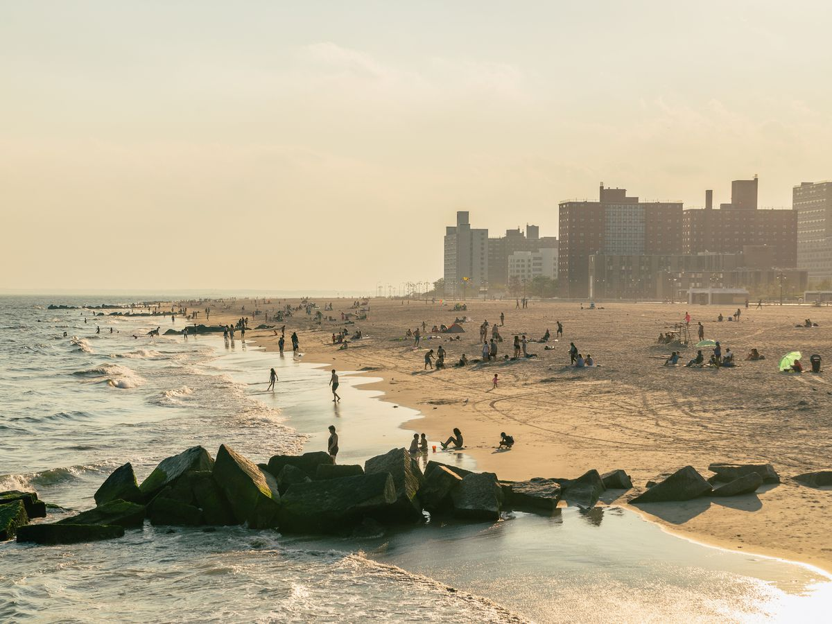In the foreground is the ocean and a beach with sand. In the distance are city apartment buildings.