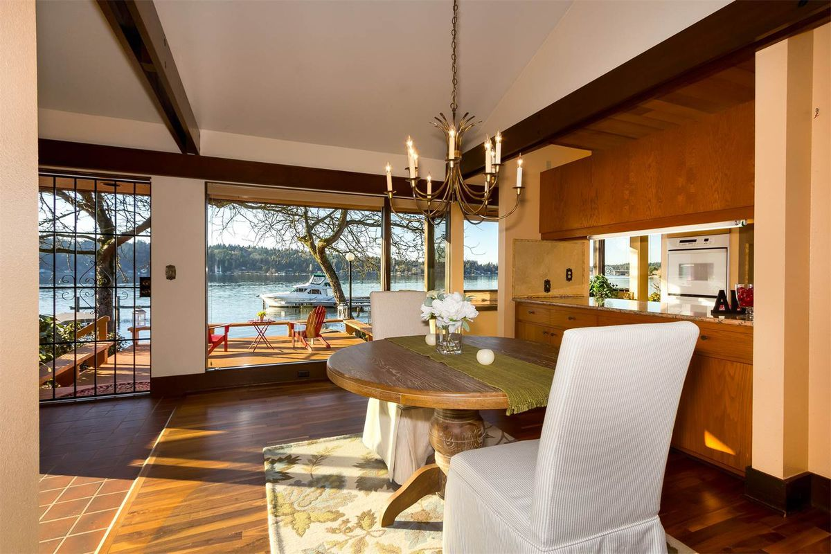 Two dining room chairs around a small table. Kitchen through breakfast island. Large window and back door lead to backyard and lake.