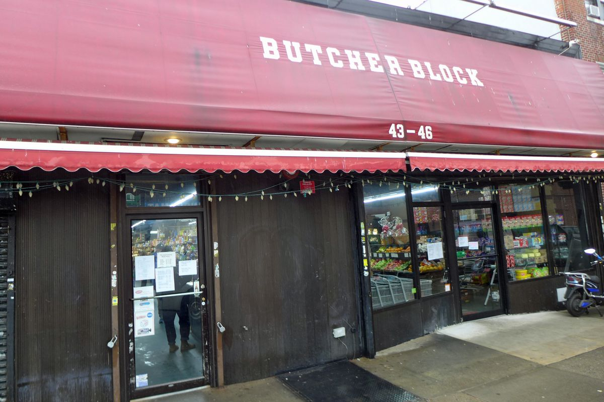 A plain storefront with a big red awning, with Butcher Block in block letters.