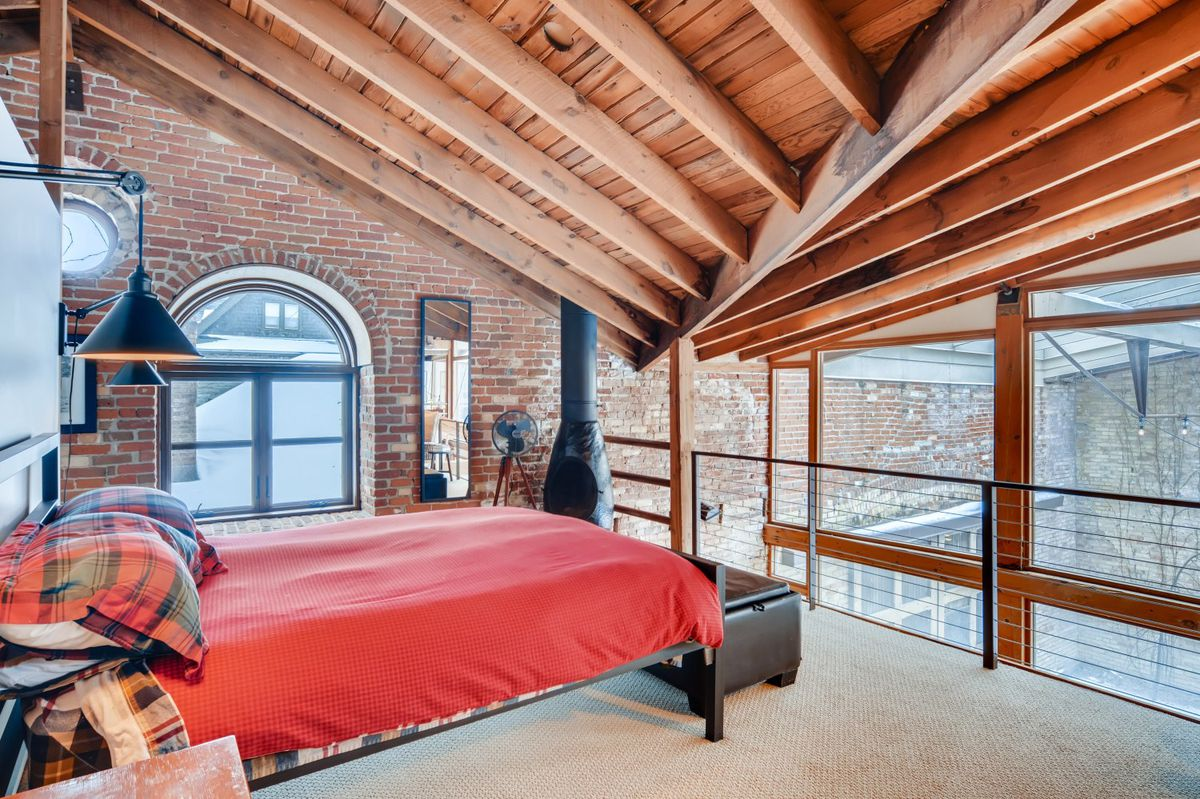 A red bed sits in a second story loft with a wood stove in the corner.