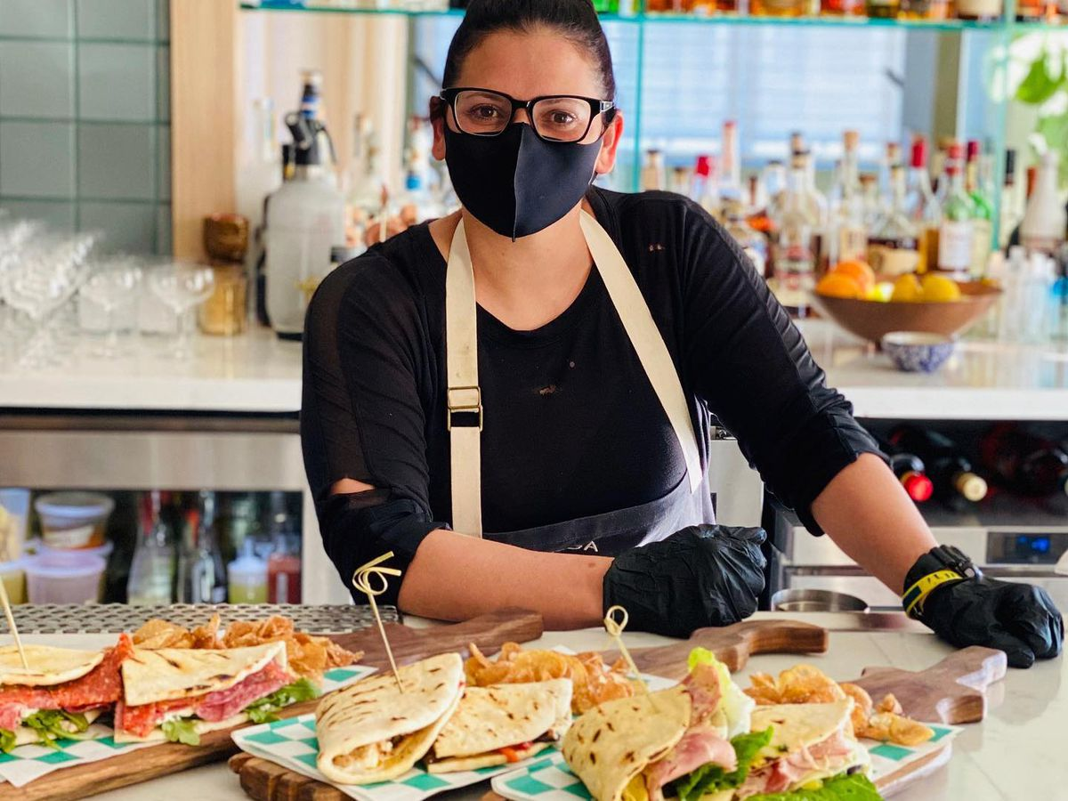A woman in black stands in front of plates with sandwiches