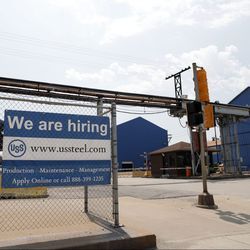 A help wanted sign hangs outside the U.S. Steel Granite City Works facility Thursday, June 28, 2018, in Granite City, Ill. After being shut down for roughly two years, the plant recently restarted one of its two idle blast furnaces with the second scheduled to come back online later this year.   AP Photo/Jeff Roberson