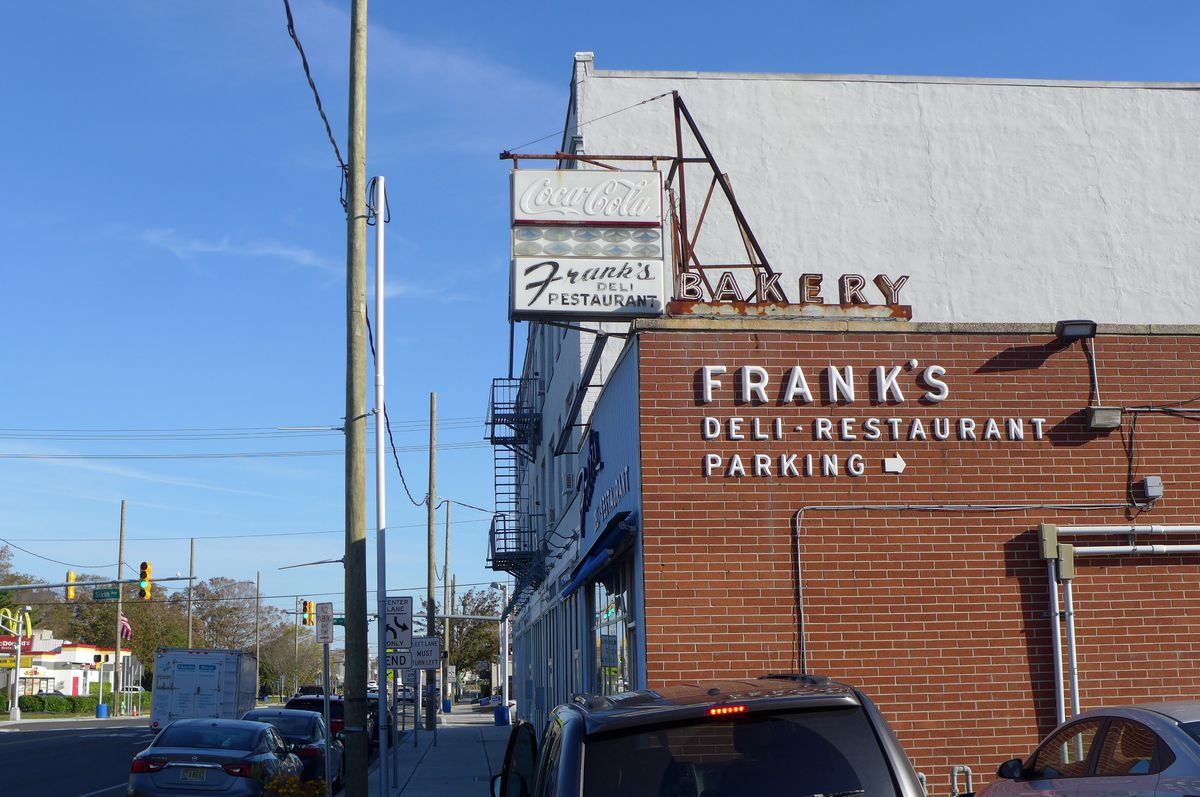 A two story brick building with several old signs on the side that read Frank's Deli.