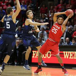 Utah Utes guard Kenneth Ogbe (25) gets caught by Brigham Young Cougars guard Kyle Collinsworth (5) and Brigham Young Cougars guard Chase Fischer (1) as Utah and BYU play in the Huntsman Center in Salt Lake City Wednesday, Dec. 2, 2015. Utah won 83-75.