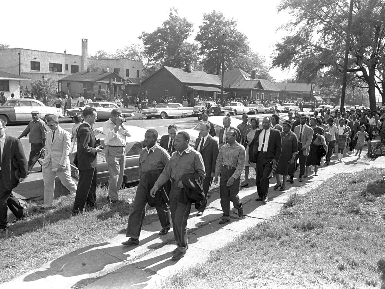 "Rev. Ralph Abernathy, left, and Rev. Martin Luther King Jr. lead a column of demonstrators as they attempt to march on Birmingham, Ala., city hall April 12, 1963. Police intercepted the group short of their goal. Rev. Jonathan McPherson, shown in a coat and tie two people behind King, in 2021 is urging protesters against racial injustice to ""keep on keeping on."""