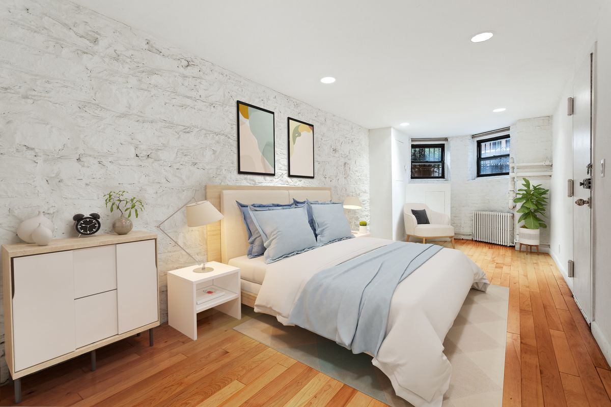 A bedroom with hardwood floors, white exposed brick, and a large bed.