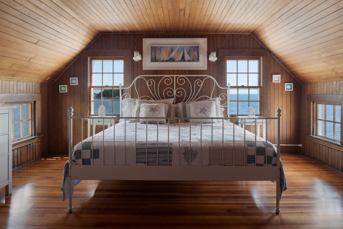 A white frame bed sits in a wood-paneled room with windows and ocean views.