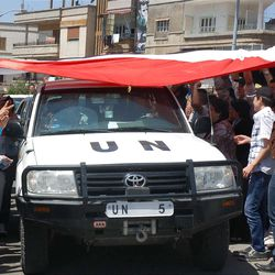 A U.N. observers vehicle passes under a huge Syrian flag held by Syrian President Bashar Assad supporters during their visit to the pro-Syrian regime neighborhoods in Homs province, central Syria.