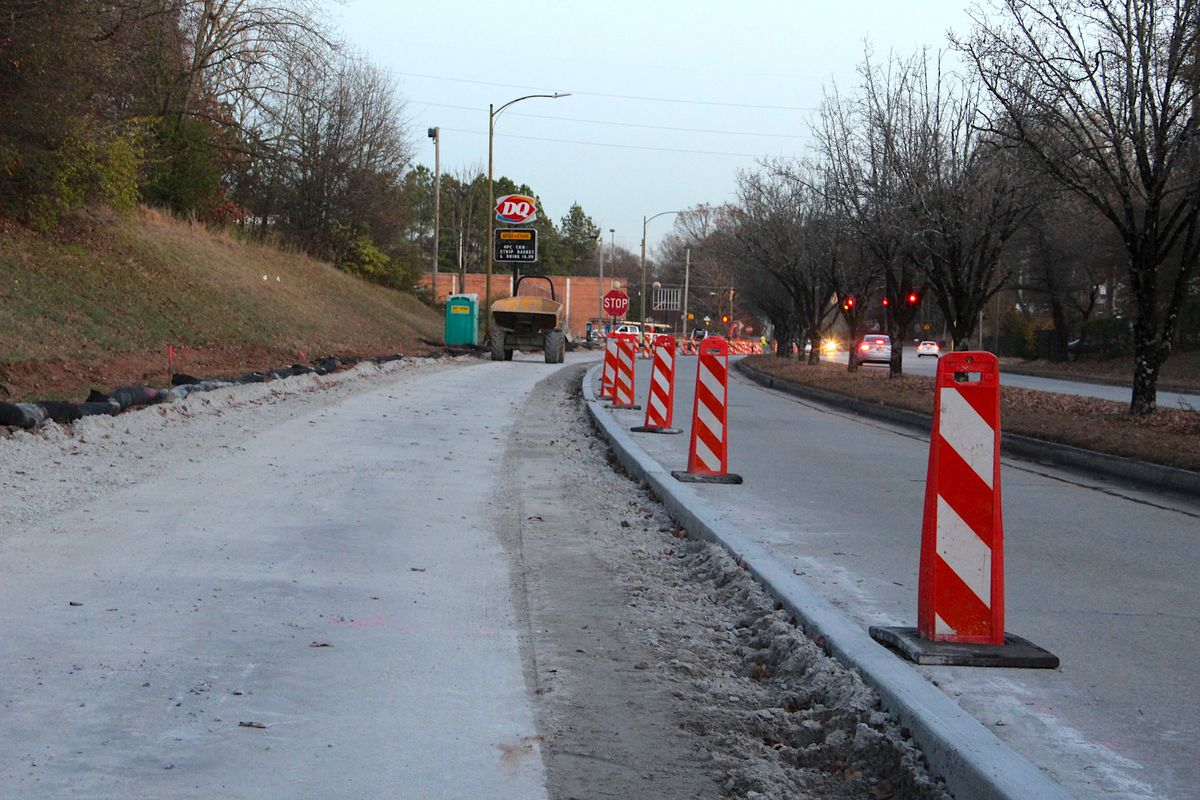 A concrete path being installed beside a roadway and a Dairy Queen in the distance.