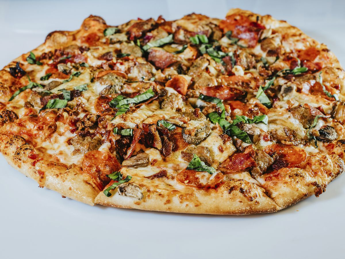 A closeup photo of the Magnificent 7 meatlovers pizza with pieces of pepperoni, sausage, bacon and basil visible on top of it