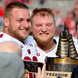 Offensive linemen David Moorman (#68) and Tyler Biadasz haul away the giant block of Freedom. The trophy stays home, as foretold by Zack Baun.