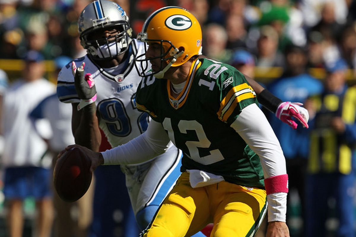 GREEN BAY WI - OCTOBER 03: Aaron Rodgers #12 of the Green Bay Packers moves to avoid Cliff Avril #92 of the Detroit Lions at Lambeau Field on October 3 2010 in Green Bay Wisconsin. (Photo by Jonathan Daniel/Getty Images)