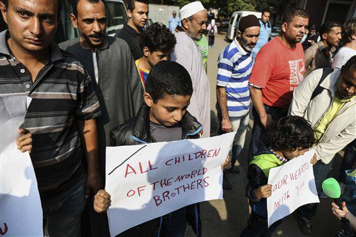 Egyptian boys hold posters to share sorrow outside Zeinhom morgue, where bodies of Russian plane crash victims were kept on Sunday, in Cairo, Egypt. | Mohammed El Raai/AP