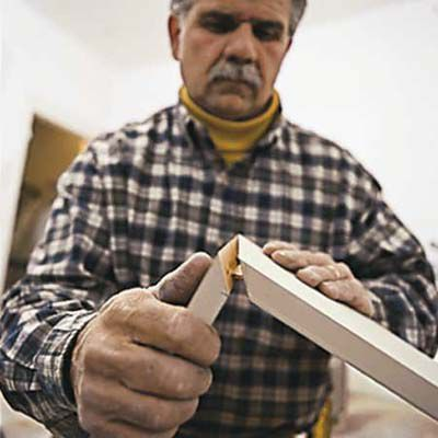 Man Assembles Biscuit Joints Of Baseboards