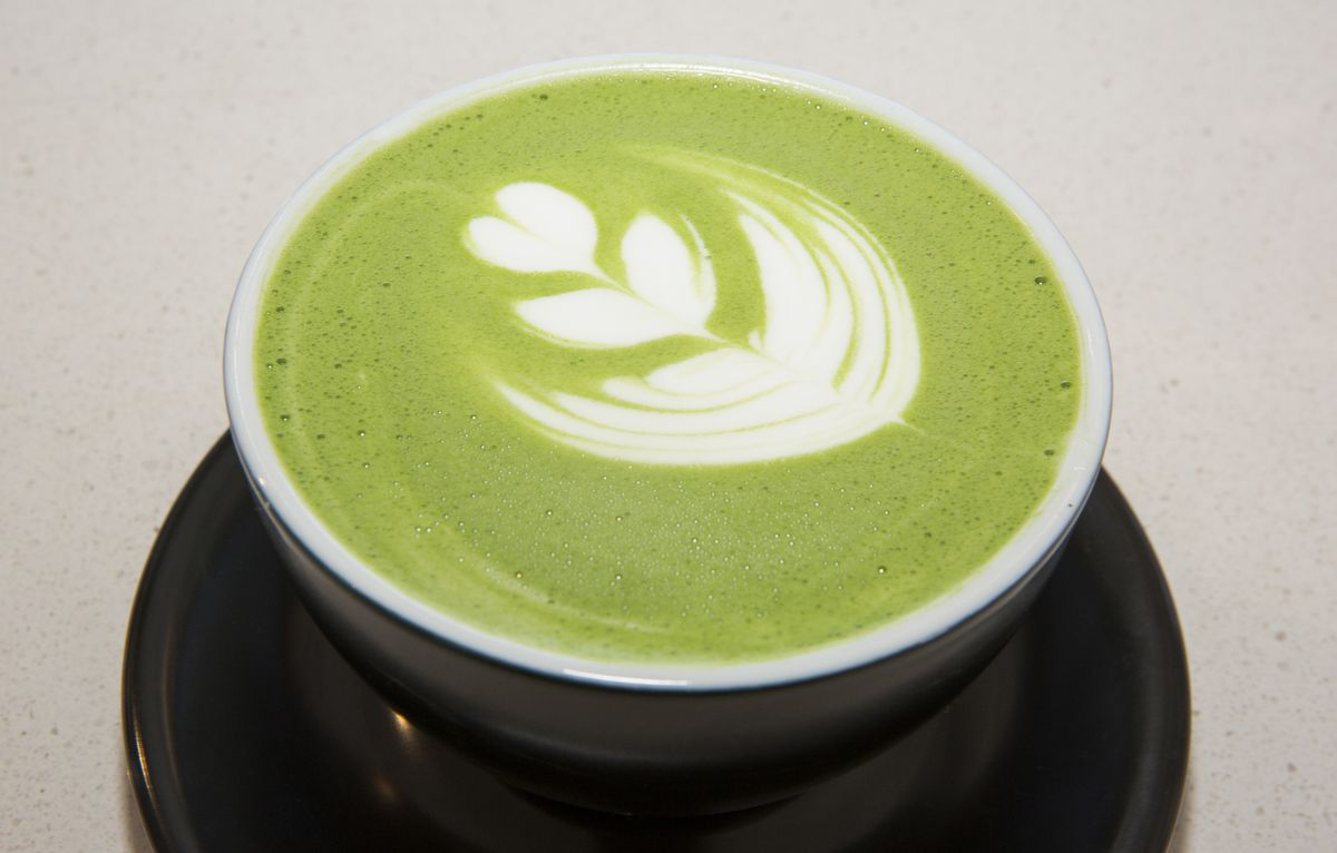 A green coffee drink in a white cup on a black saucer.