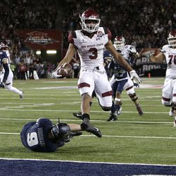 New Mexico State running back Larry Rose III (3) leaps over Utah State linebacker David Woodward to score a touchdown in overtime and  win the Arizona Bowl NCAA college football game, Friday, Dec. 29, 2017, in Tucson, Ariz. (AP Photo/Rick Scuteri)