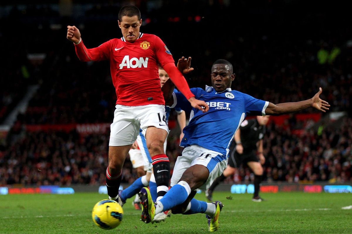 Javier Hernandez of Manchester United is tackled by Maynor Figueroa of Wigan Athletic during the Barclays Premier League match between Manchester United and Wigan Athletic at Old Trafford.