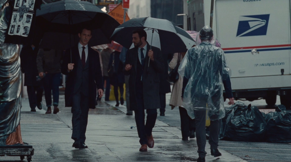 Kendall and his friend walking down the street with giant black umbrellas as another man tries to walk by them in a clear poncho