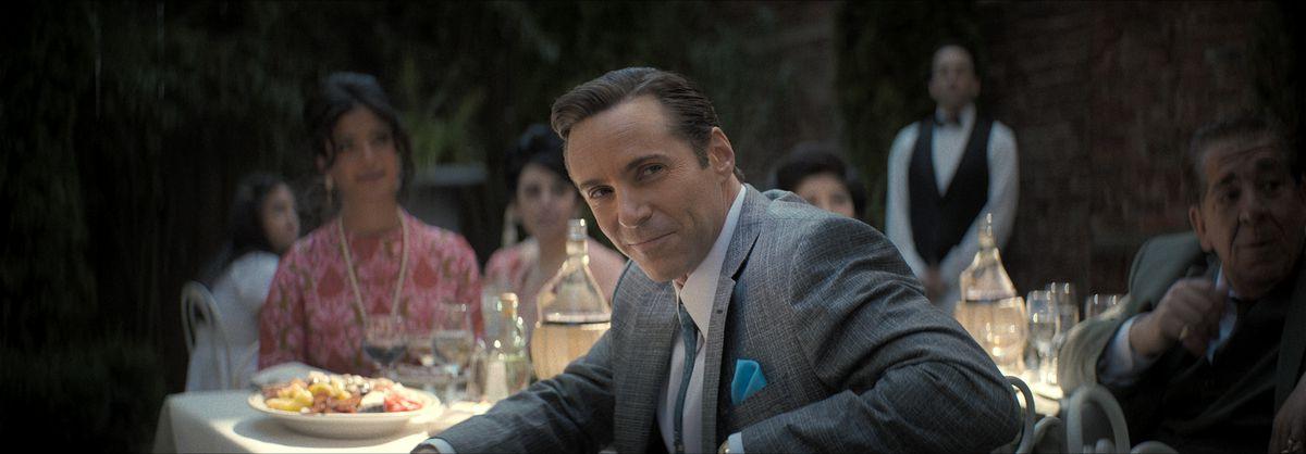 Alessandro Nivola as Dickie Moltisanti smirks from the dinner table in The Many Saints of Newark