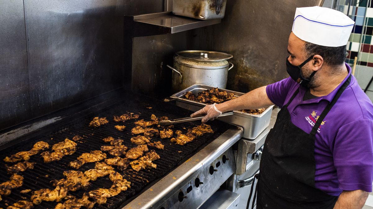 Man wearing a purple polo and chef's hat mans a grill filled with several pieces of chicken.