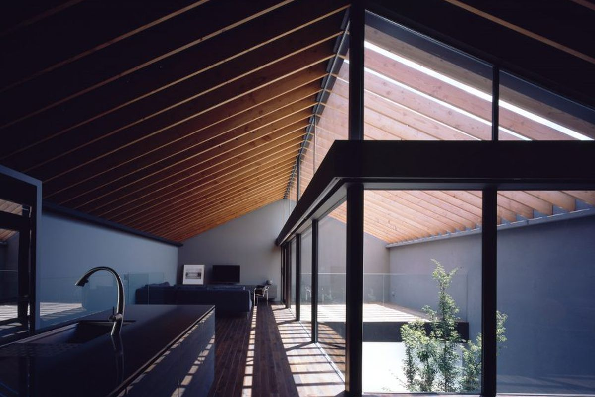 Living room with slanted and exposed timber ceiling beams.