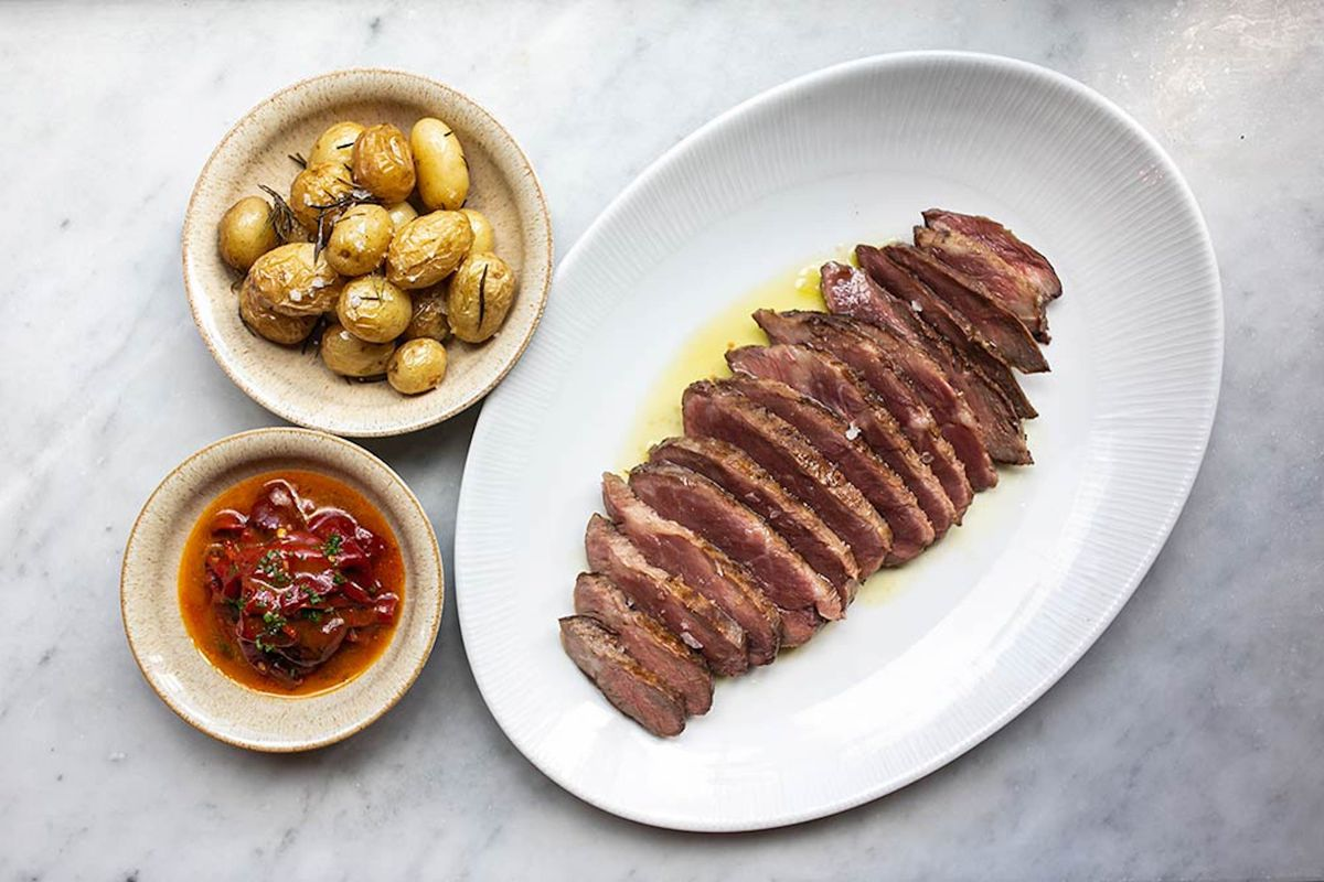 Ibérico presa with potatoes and caramelised red peppers, served on a white platter on a marble-esque background