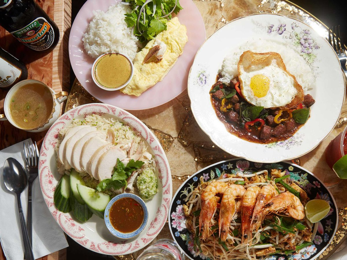 A spread of food from Uncle Boons Sister, including poached chicken, pad thai with prawns, and a beef scramble with eggs.