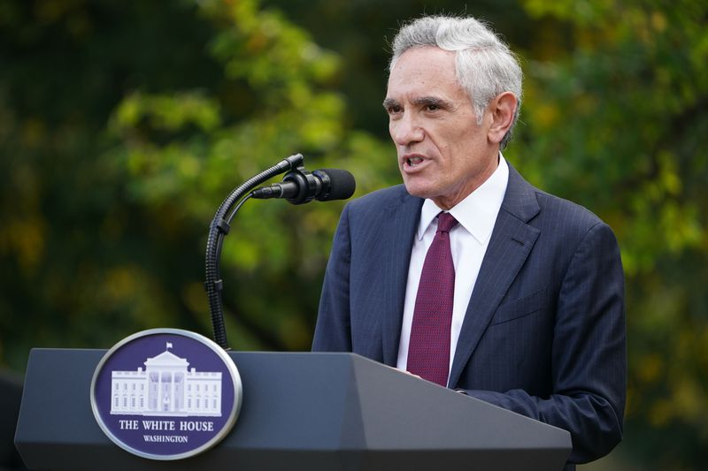 Atlas, silver-haired, in a blue suit and burgundy tie, speaks into a microphone at a podium outdoors.