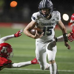 Corner Canyon's QB Devin Brown runs through American Fork's Davis Andrews (12)and Kyle Moore (11) at American Fork High School on Friday, Sept. 17, 2021.