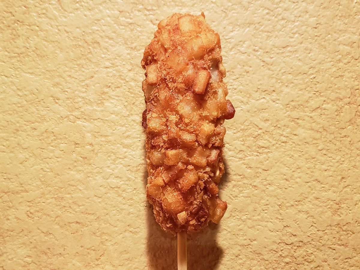 A corn dog with crispy batter against a tan wall.
