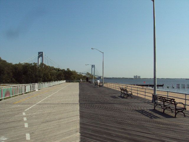 A beach boardwalk. There are benches on one side of the boardwalk and trees on the other side of the boardwalk. In the distance is a bridge.